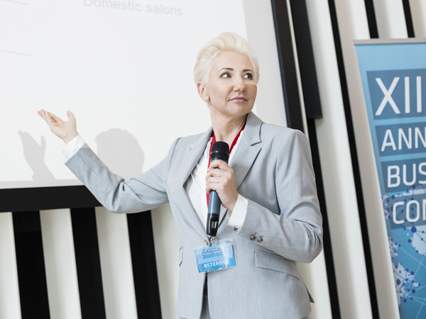 Woman speaking with a microphone at a business conference